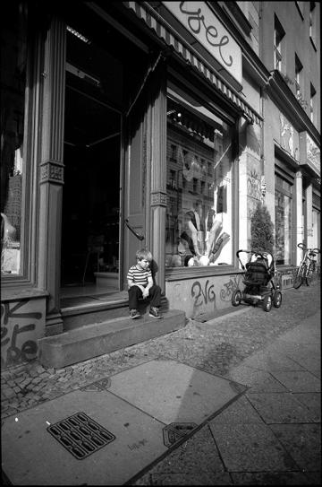 Das Einkaufen hat den Jungen auf der Ladentreppe offensichtlich ziemlich erschöpft. Oranienburger Straße, Kreuzberg