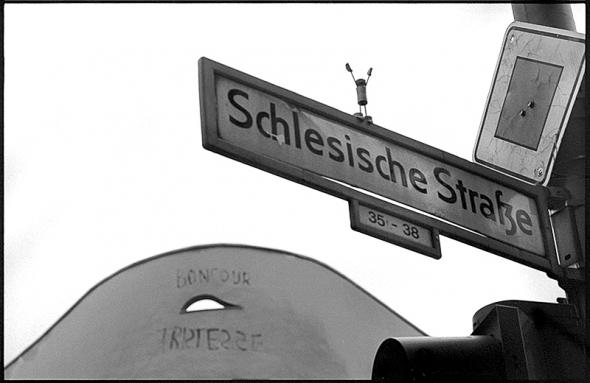 Aus Kork gefertigte Yoga Figur auf einem Strassenschild in Berlin Kreuzberg